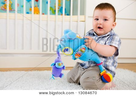 Happy baby boy ( 1 year old ) sitting on floor at home and playing with soft toys at children's room, smiling.
