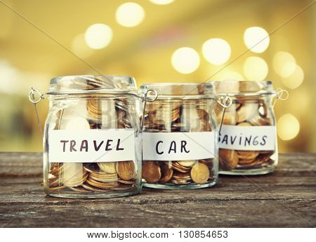 Three jars for different needs full of coins on bright background