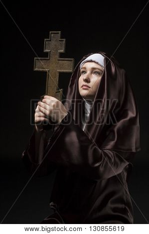Young catholic nun is praying. Orthodox cross in her hands. Photo on black background.