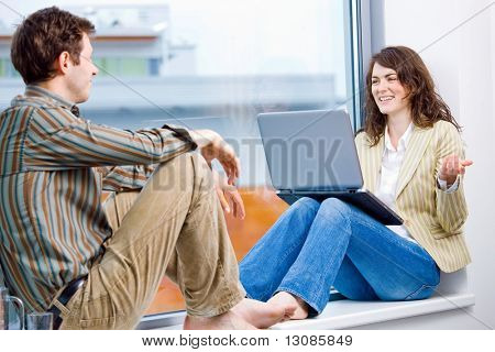 Businessman and businesswoman having creative meeting,  sitting in office window working on laptop computer and talking.