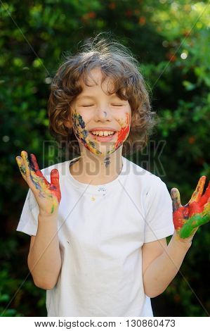 Boy has fun with the painting and show his dirty hands into the camera. Boy closed his eyes in pleasure. Children's creativity. Art for baby. Emotions. Delight.