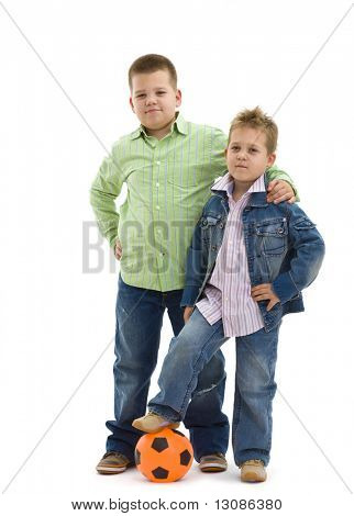 Young boys wearing trendy jeans clothes posing together with football, on isolated white background.