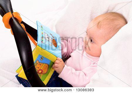 Baby Spiel mit Märchenbuch im Tragetuch sitzen.
