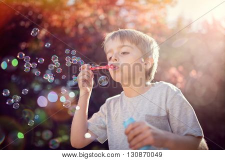Little boy playing with bubble wand blowing soap bubbles in summer sunshine