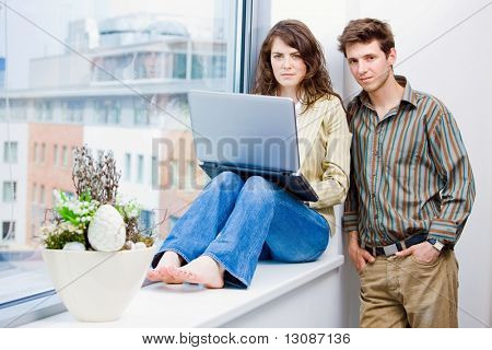 Male and female office workers talking and brainstorming at office, using laptop computer.