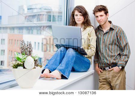 Maschio e femmina impiegati parlando e brainstorming in ufficio, utilizzando il computer portatile.