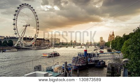 London, England - July 26, 2014 - Sunset in London over the Thames river in Westminster with the London eye and Big ben in the background. London is the capital city of England and a popular tourist destination.