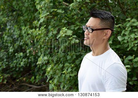 A mature asian man gazing afar at outdoor