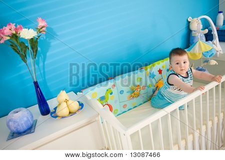 Baby boy ( 1 year old ) playing in baby bed at children's room.