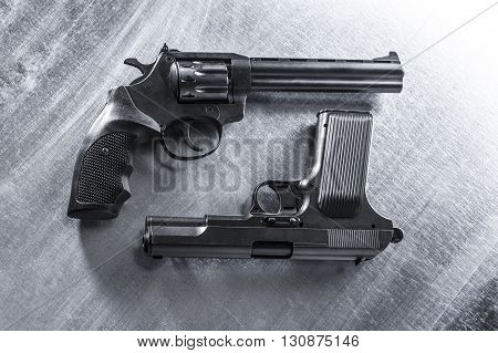semiautomatic pistol and revolver on metal background.