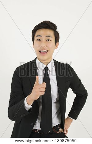 Asian young businessman pointing at you with index finger