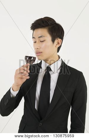 Asian young businessman holding glass of red wine