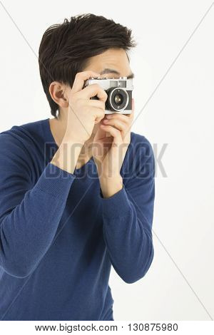 Asian young man taking photo by a old film camera