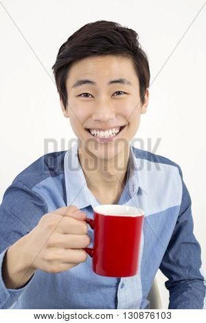 Asian handsome young man holding a red mug
