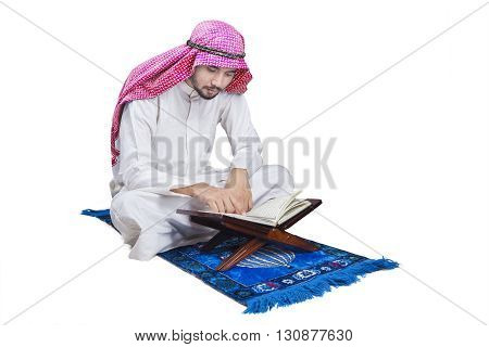Portrait of Arabic person sitting on the carpet while reading Quran in the studio isolated on white background