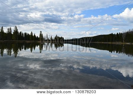 The clouds of a passing storm reflects in the yellowstone river
