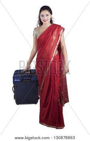 Beautiful Indian woman wearing saree clothes and carrying a suitcase while walking in the studio isolated on white background