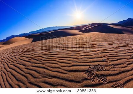 Bright solar morning in picturesque part of Death Valley, USA. Mesquite Flat Sand Dunes, Stovepipe Wells Village. Thin waves on sand