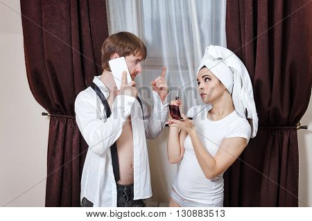Morning couples. Husband and wife are going to work. Man talking on the phone. Girl doing make-up with a towel on her head.