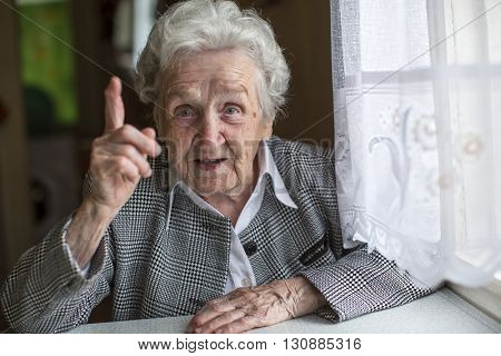An elderly woman sitting at a table and specifies the finger.