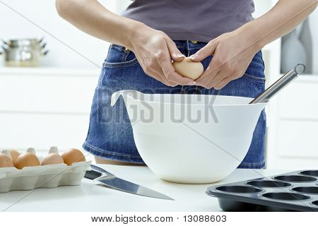 Female hands breaking eggs into a bowl.