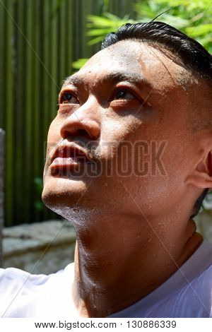 An Asian man sweating profusely under the hot sun