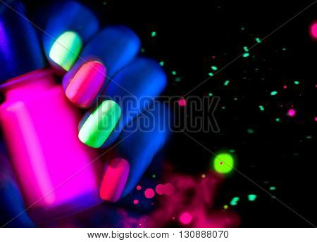 Neon Nails. Fashion model woman nails in neon light, beautiful nail art with fluorescent nail polish, Art design of female colorful disco nailart in UV, Isolated on black background