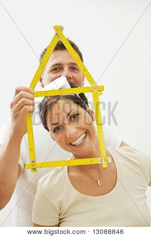 Portrait of happy couple dreaming of new house, smiling. Isolated on white background.