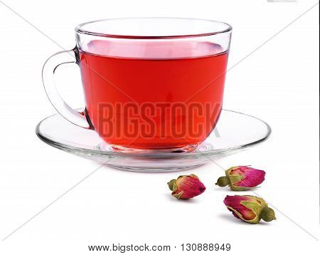 Glass transparent cup of rose tea on a saucer and three buds dried roses isolated on white background.