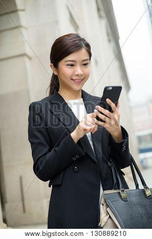 Asian businesswoman sending sms on mobile phone