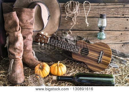 ukulele with american west rodeo brown cowboy hat and leather boots in vintage ranch barn studio background Still life style