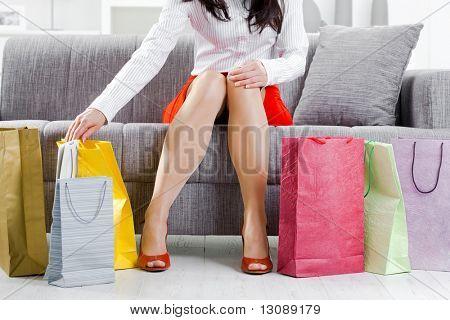 Mujer joven sentada en el sofá después de día de compras, embalaje bolsas coloridas.
