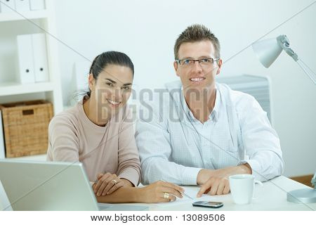 Happy young casual couple sitting  at desk working together at home office, smiling.