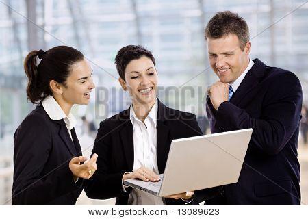 Drei junge Unternehmer stehen in der Lobby, Blick auf Laptop-Computer-Bildschirm, lächelnd.