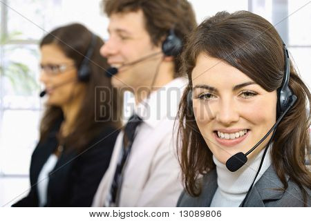 Three young customer service operators sitting in a row and talking on headset. Selective focus on women in front.