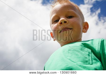 Cute little boy against blue sky with white clouds smiling and winking with cheeky look on his friendly face