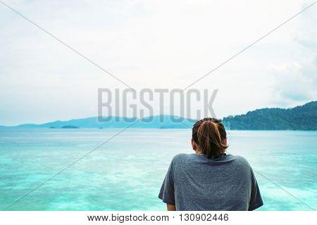 a girl looking to blue ocean, vintage tone