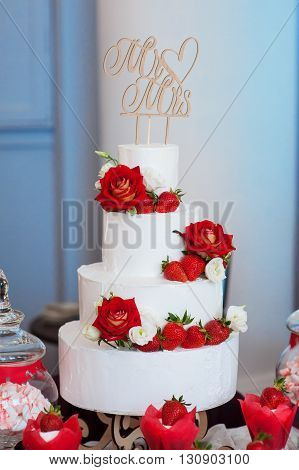 four-layer white wedding cake with red roses and strawberries.