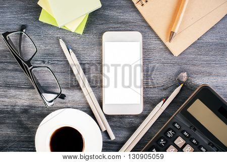Top view of wooden desktop with blank white smart phone glasses coffee cup calculator and stationery. Mock up