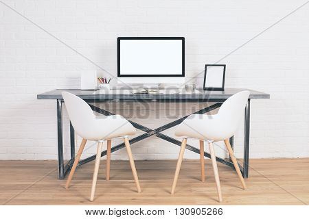 Two chairs next to designer table with blank white computer screen and other items on wooden floor and brick background. Mock up