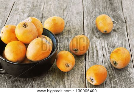 Tasty, yellow loquats on the wooden background