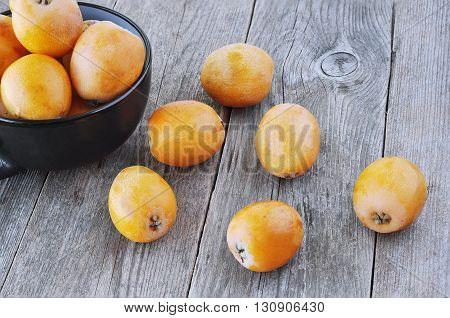 Tasty yellow loquats on the wooden background.
