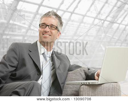 Businessman wearing grauen Anzug und Gläser, sitzen auf der Couch mit Laptop-Computer im Büro Lobby, sm