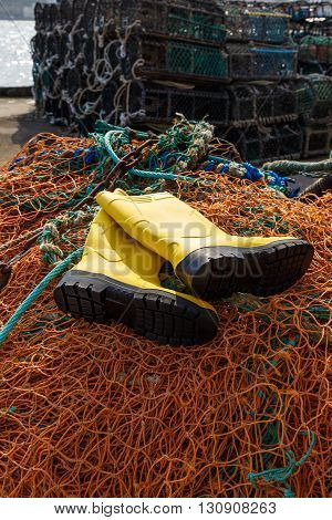 SCARBOROUGH ENGLAND - MAY 5: Trawlerman's protective boots commercial fishing nets and lobster pots in the harbour. In Scarborough England. On 5th May 2016.