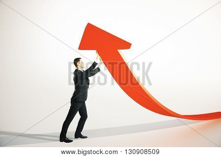 Success concept with businessman upholding red arrow on light grey background