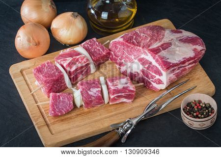 Raw pork meat cut into cubes ready for bbq kebab on black background
