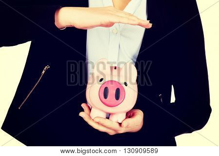 Young business woman protects piggybank.