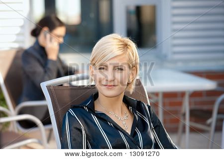 Portrait of attractive young businesswoman sitting in chair outdoor, smiling.