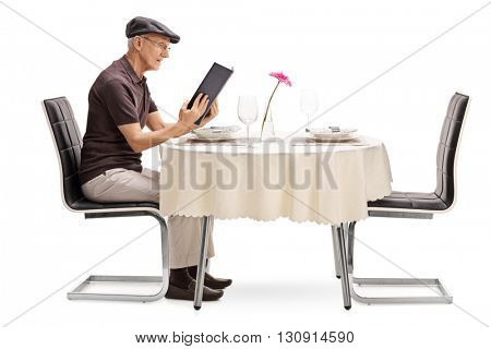 Senior man sitting at a restaurant table and looking at the menu isolated on white background
