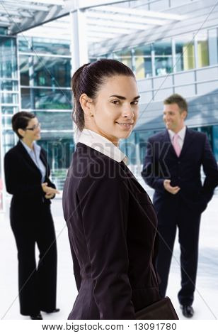 Young businesswoman standing in front of office building, looking back, smiling.